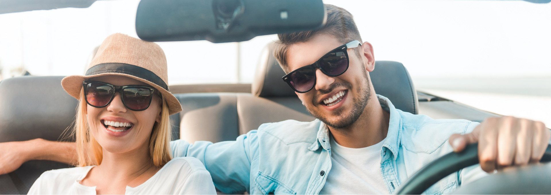Smiling couple wearing sunglasses driving in a vehicle