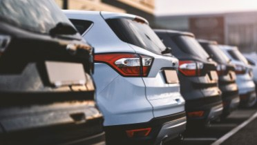 Close-up of the rear of new vehicles parked next to each other