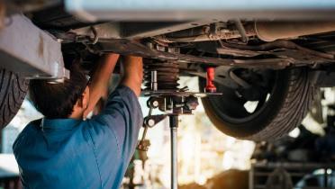 Car mechanic fixing bottom of vehicle: