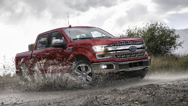 Front side view of Ford F-150 in red driving through a mud puddle