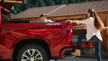 Woman stepping up into a truck cargo bed