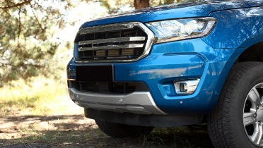 Close-up of a blue truck and its grille