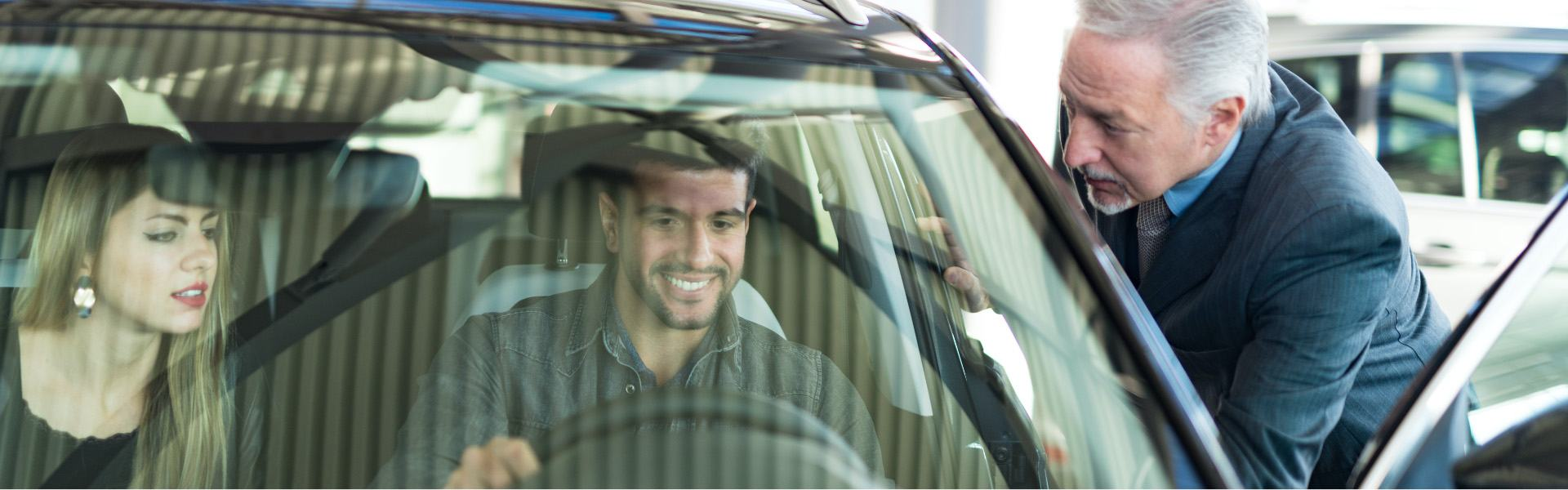Smiling couple in a car with a salesperson outside