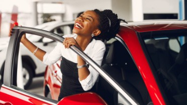 Happy person exiting a red car
