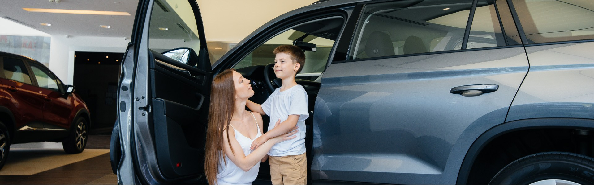 Adult and child standing beside a grey minivan with its door open