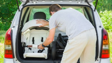 Person placing a baby stroller in the back of a white minivan