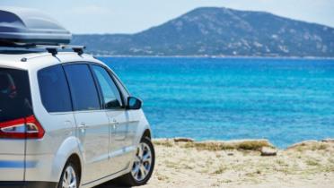 Silver minivan parked on a beach shore