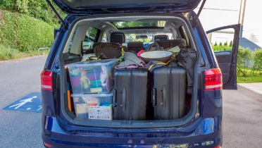 Blue minivan with gear packed in the back