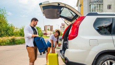 Family packing luggage in the trunk of an SUV