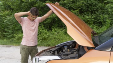 Person inspecting under the hood of an orange SUV