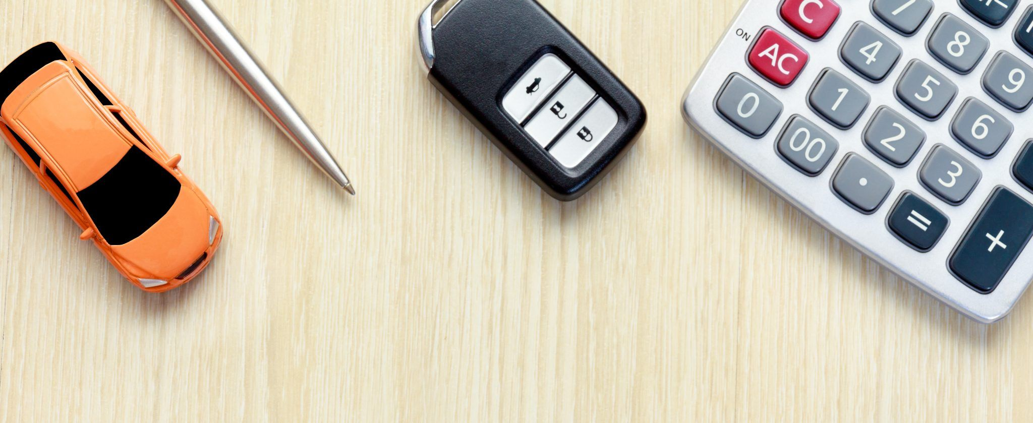 Overhead view of toy car, pen, key fob and calculator