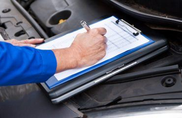 Person writing on clipboard on open front of vehicle