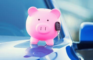 Piggybank with a key stuck to it on a car in front of a building