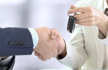 Customer and salesperson shaking hands and handing over keys