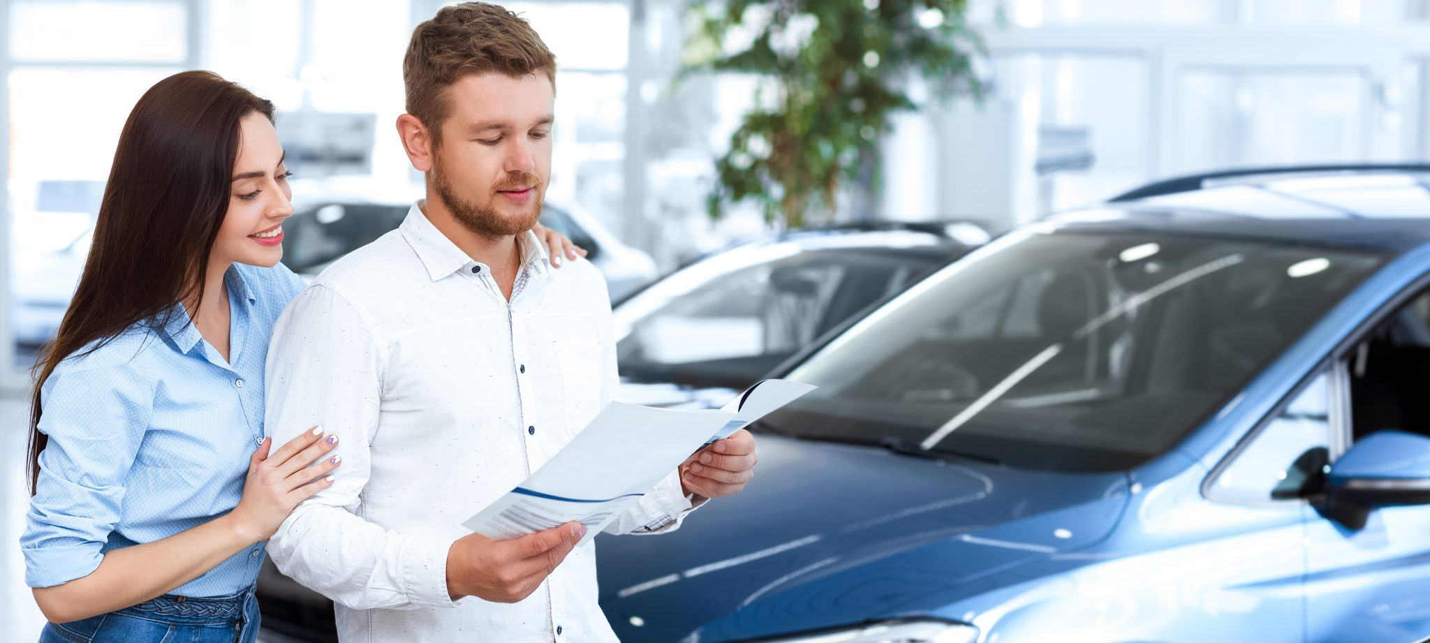 Couple in dealership looking over a document