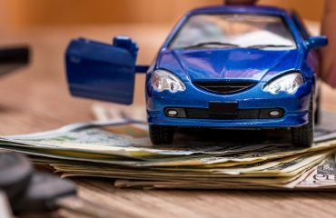Toy car on cash behind car keys and coins