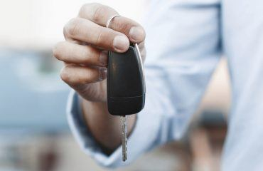 Keys held up by a hand in front of out of focus vehicle
